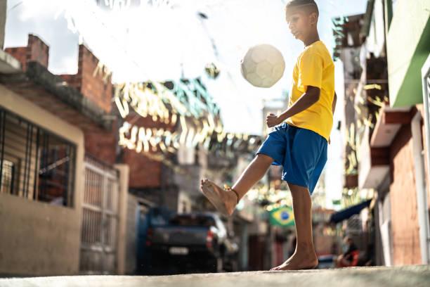 braziliaanse kid te voetballen in de straat - internationaal voetbalevenement stockfoto's en -beelden