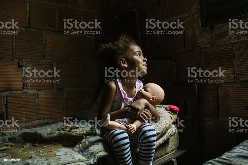 Brazilian little girl holding a doll in the bedroom stock photo