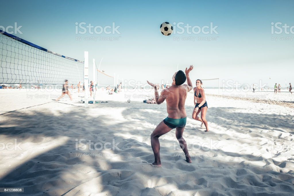 brazilian man and woman playing footvolley at beach in Rio de Janeiro stock photo