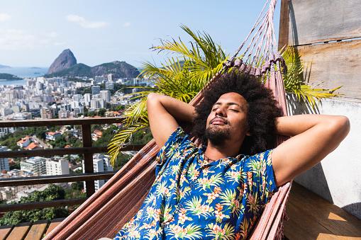 Young man sleeping in Hawaiian shirt, relaxing on balcony, sunbathing in Rio de Janeiro