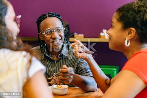 Close up of three friends having eating in acai cafe, smiling and looking happy, talking over traditional Brazilian cuisine