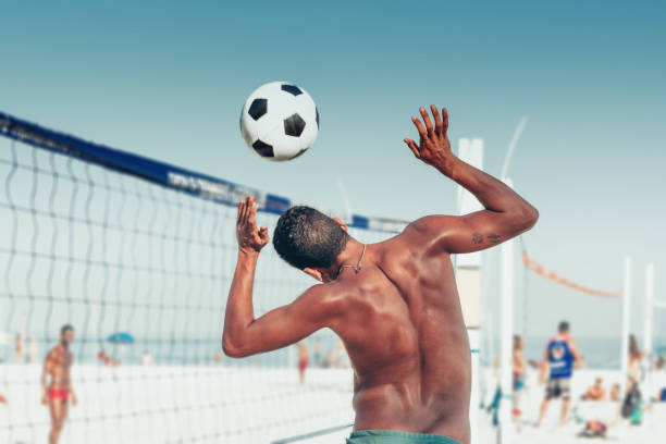 brazilian man heading soccerball over volleyball net at beach stock photo