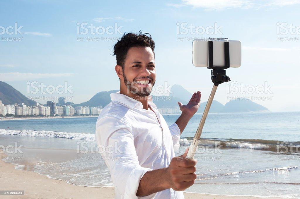 Brazilian man making selfie with stick at Copacabana stock photo