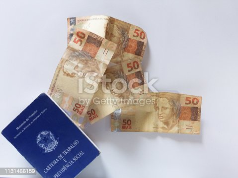 istock Brazilian money (real notes) flying from the work document and social security document (carteira de trabalho). Success or crisis  concept. Blurry Image. 1131466159