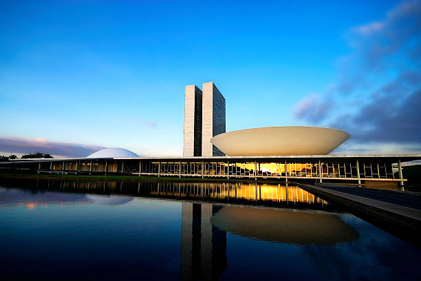 Brazilian National Congress at Sunset Brasilia, Federal District, Brazil - May 27, 2007: Brazil's Bicameral National Congress is part of the city's main monuments and was projected by the brazilian architect Oscar Niemeyer. Since the 1960s, the National Congress has been located in Brasília. The semi-sphere on the left represents the Senate, and the semi-sphere on the right is the Chamber of the Deputies. brazilian culture stock pictures, royalty-free photos & images