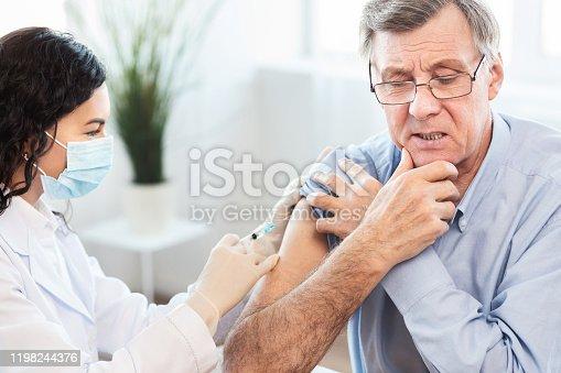 917598714 istock photo Brazilian nurse doing vaccination to senior man 1198244376