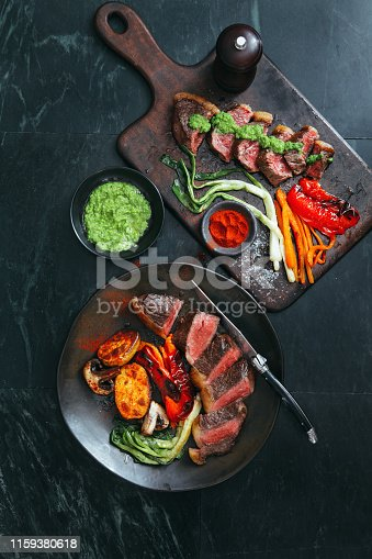 808351106 istock photo Brazilian picanha steak with fresh herb sauce and grilled vegetables 1159380618