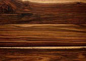 Closeup of panels of Brazilian Rosewood background surface showing light and dark patterns of wood grain texture.