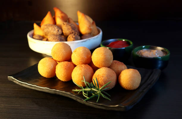 Brazilian snack bolinha de queijo, deep fried balls stuffed with cheese on dark background. Selective focus. stock photo