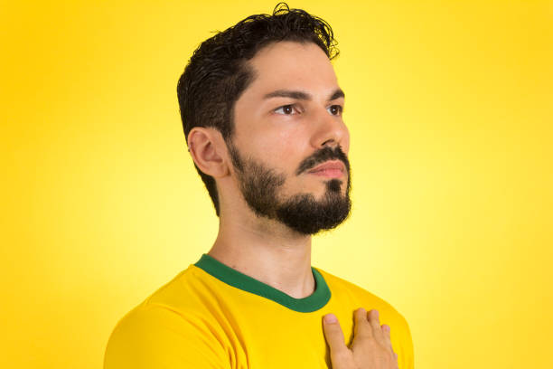brazilian soccer football player listening to the anthem and hand over the chest. - national anthem stock photos and pictures