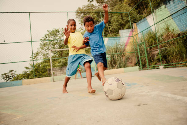 Brazilian Soccer Two boys from the favelas in Rio de Janeiro challenge each other for the soccer ball on a concrete pitch. brazilian culture stock pictures, royalty-free photos & images