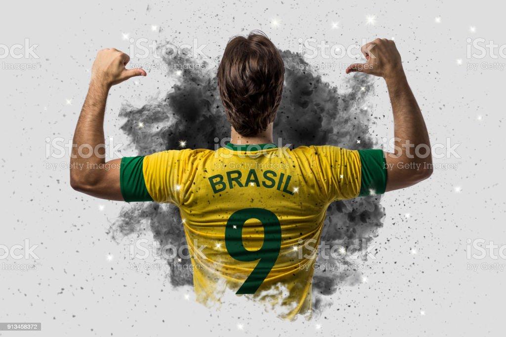 Jogador de futebol brasileiro, saindo de uma explosão de fumaça. comemorando. - foto de acervo