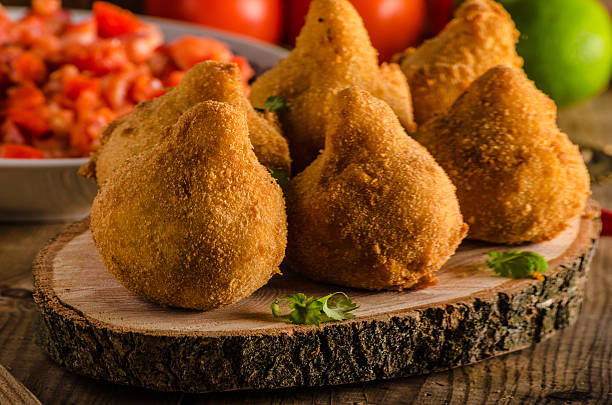 Brazilian Street Food Coxinhas Delicious food consisting of chopped or shredded chicken meat, covered in dough, molded into a shape resembling a chicken leg, battered and fried, with hot salsa, rustic photo coxinha stock pictures, royalty-free photos & images