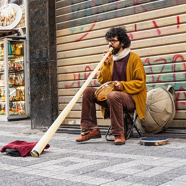 brazilian street musician in turkey plays caribbean drum and didgeridoo - didgeridoo stock photos and pictures