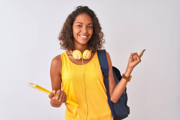 mujer estudiante brasileña con mochila sosteniendo cuaderno sobre fondo blanco aislado muy feliz señalando con la mano y el dedo hacia un lado - estudiante fotografías e imágenes de stock