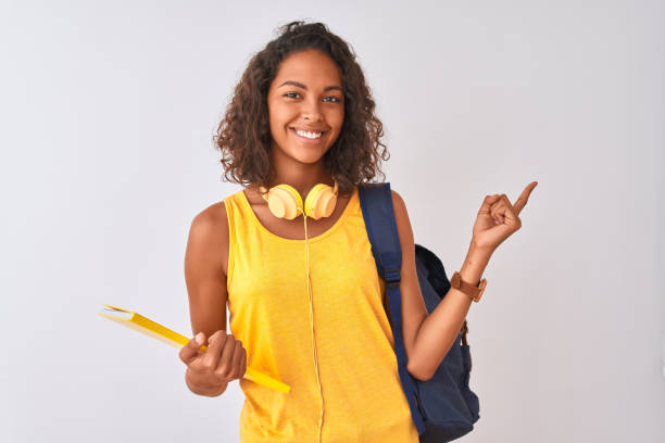 brazilian student woman wearing backpack holding notebook over isolated white background very happy pointing with hand and finger to the side - studenti foto e immagini stock