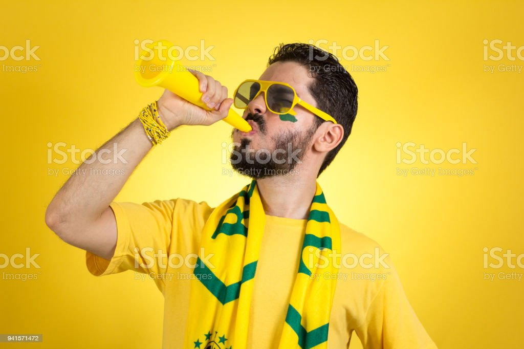 Brazilian supporter of National football team is celebrating, cheering. Male fan. stock photo