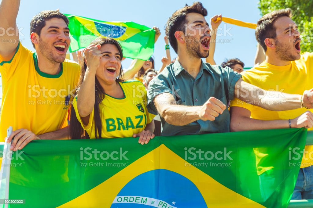 Brasileiros torcedores comemorando no estádio com bandeiras - foto de acervo