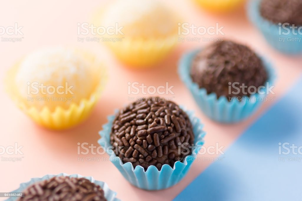 Brazilian sweets: Beijinho and Brigadeiro. Children birthday parties. Candy balls in a straight line. Colorful background. stock photo