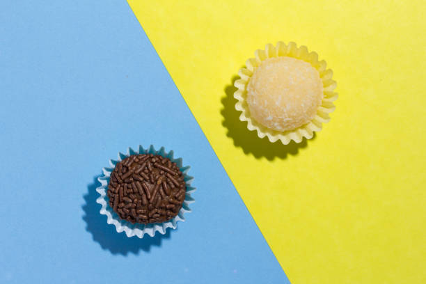 Brazilian sweets: Beijinho and Brigadeiro. Children birthday parties. Flat design of candy ball on color background. stock photo