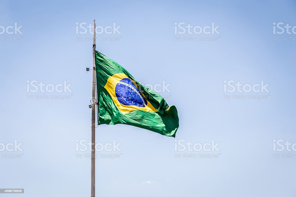 Brazilian waving flag on blue sky stock photo