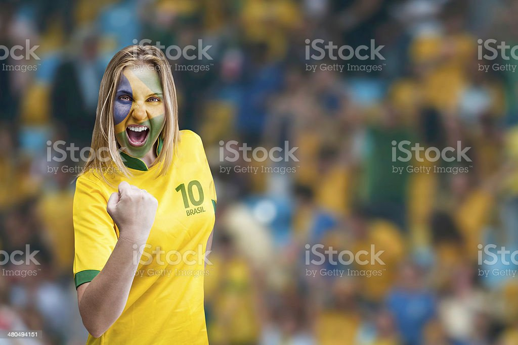 Brazilian woman celebrates on the arena with her face painted stock photo