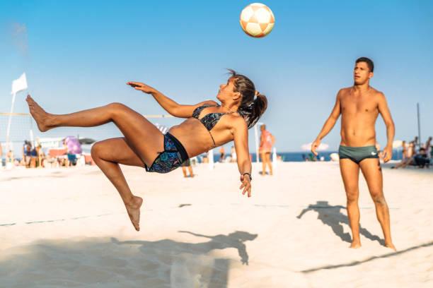 Brazilian woman jumping and kicking ball on beach in Brazil stock photo