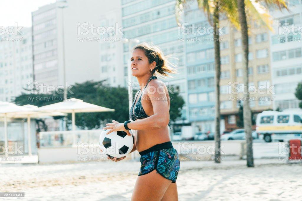Brazilian woman with soccer ball on beach, Rio de Janeiro, Brazil stock photo