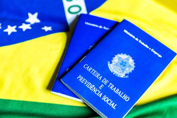brasilianische arbeitsdokument und soziale sicherheitsdokument (portugiesisch: carteira de trabalho) auf brasilianische flagge - wirtschaftsrecht stock-fotos und bilder