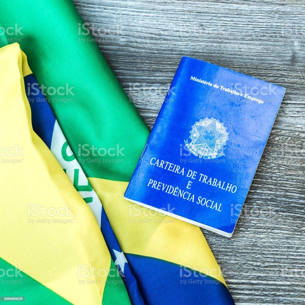 Brazilian work document and social security document (Portuguese: Carteira de Trabalho) on brazilian flag stock photo