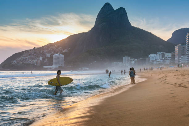 Brazilian young man walking on Ipanema Beach with surfboard stock photo