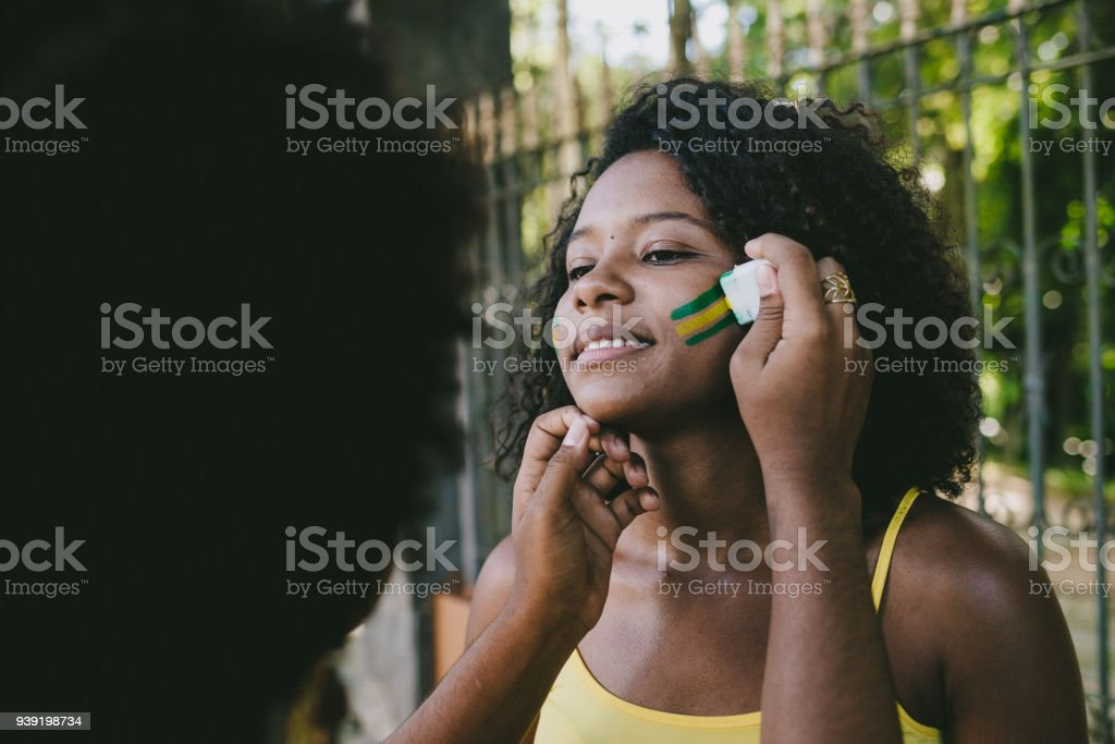Brazilian young woman fan making up with the colors of Brazil stock photo