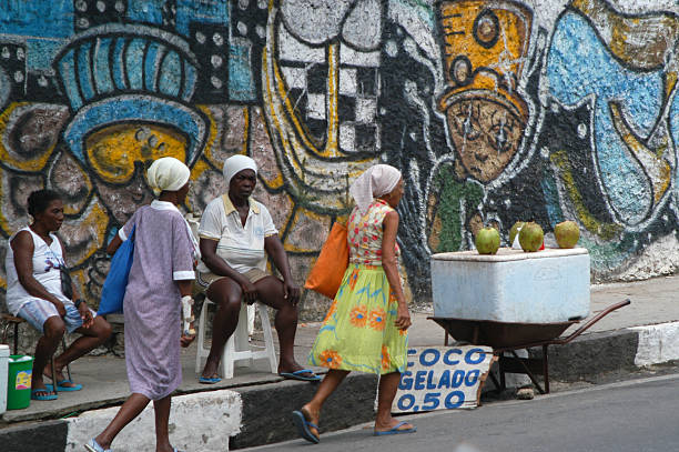 Brazilians Pass Coco Gelado Stand in Salvador Brazil Salvador, Brazil - March 21, 2003: Brazilian women pass a vendor selling coconut water along a street lined with colorful graffiti. Along with economic growth, prices for basic goods have skyrocketed across the country, raising concerns of social inequality.  gelado stock pictures, royalty-free photos & images