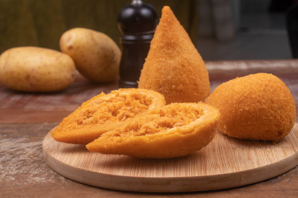 Brazlian Chicken Coxinha Brazlian Chicken Coxinha over a wooden table coxinha stock pictures, royalty-free photos & images