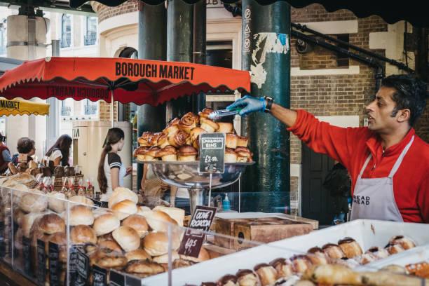 brot und eine auswahl an feingebäck zum verkauf an borough market, london, uk, verkäufer eine abholung mit riemen. - hausgemachte gebackene donuts stock-fotos und bilder