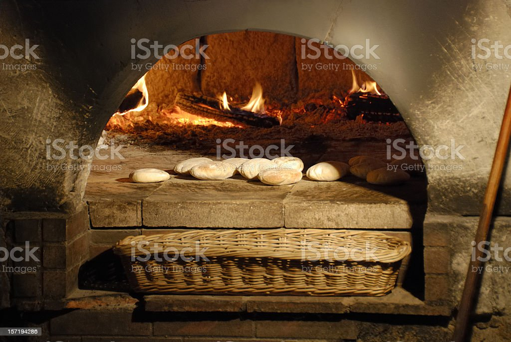 Bread and basket in front of ancient burning wood oven  stock photo