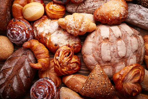 Fresh tasty bread and buns over wooden background