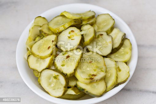 An overhead close up horizontal photograph of a white bowl full of sweet,freshly marinated bread and butter pickles