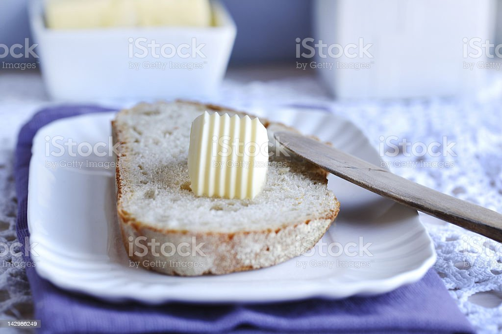 Bread and butter with a wooden knife for breakfast stock photo