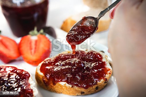 Hand with spoon pouring homemade organic strawberry jam over slices of bread with butter  on a white plate at wooden table. Served with glass of fresh milk.
