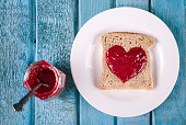 Bread and jam in heart shape on blue rustic wooden table