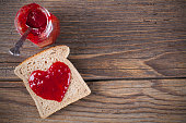 Slice of bread with strawberry jam in heart shape on rustic wooden table