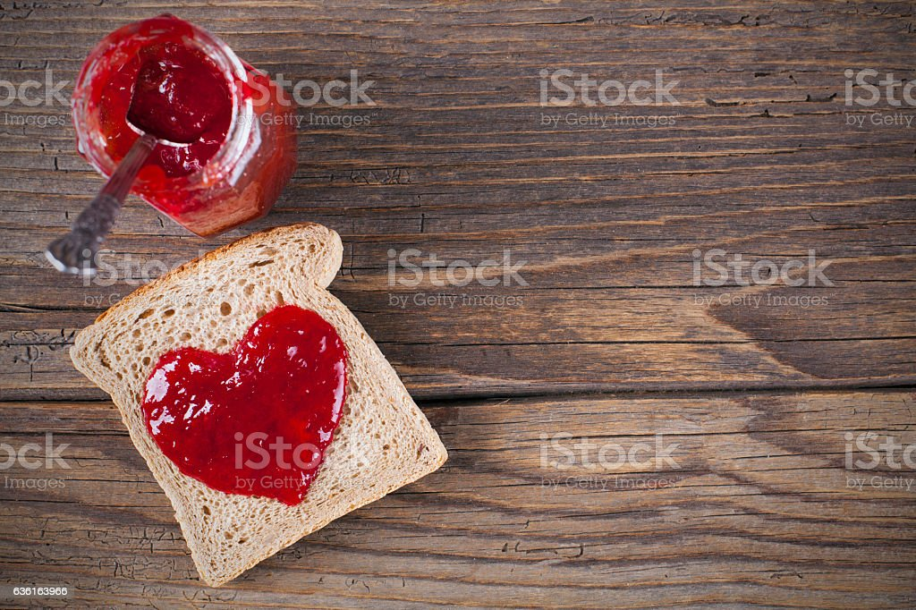 Bread and jam in heart shape on rustic wooden table stock photo