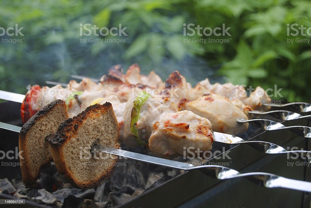 Bread and meat on skewers grilling outdoors royalty-free stock photo