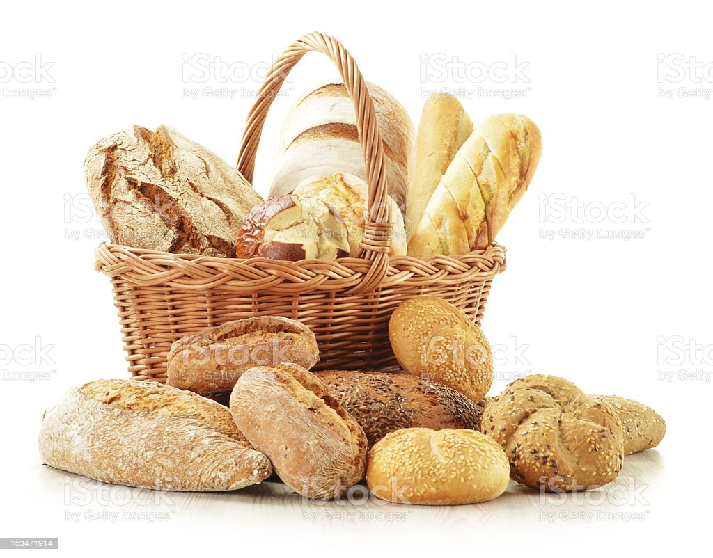 Bread and rolls in wicker basket isolated on white stock photo