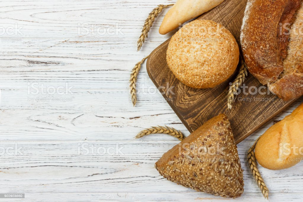 Bread and wheat on white wooden background stock photo