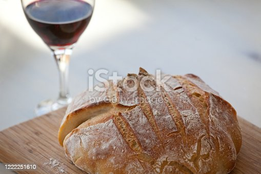 A loaf of bread and red wine for communion. Christian or religious theme.