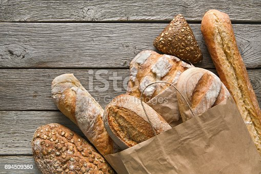 istock Bread bakery background. Brown and white wheat grain loaves composition on rustic wood 694509360
