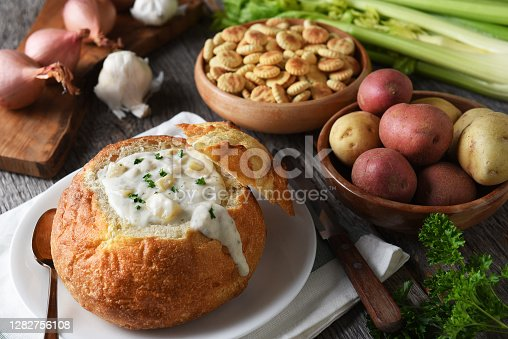 istock A bread bowl full of freshly made clam chowder with crackers and ingredients. 1282756108