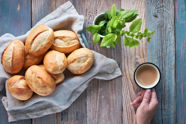 Bread buns in basket on rustic wood, spring leaves and hand with cup of coffee stock photo